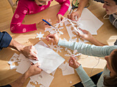 Caucasian family cutting out paper snowflakes, Jersey City, New Jersey, USA