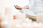 Hispanic woman meditating in lotus position near lit candles, Jersey City, NJ, USA