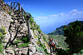 Woman hiking uphill, Macizo de Anaga mountain range, Chamorga, Tenerife, Canary Islands, Spain