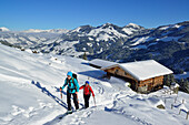 Two female back-country skiers ascending to mount Steinberg, alpine hut in background, Kitzbuehel Alps, Tyrol, Austria