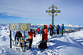 Back-country skiers beside a summit cross with signs of world religions, Kleiner Gilfert, Tux Alps, Tyrol, Austria
