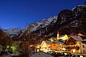 Beleuchtete Häuser und Kirche vor Bergkulisse, Innerpflersch, Pflerschtal, Stubaier Alpen, Südtirol, Italien