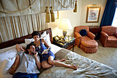 Couple lying on a hotel bed while reading a book, Istanbul, Turkey