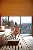 Woman sitting in a sauna of a hotel, Klais, Krun, Upper Bavaria, Germany