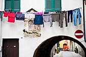 Washing hanging above an alley, Albenga, Province of Savona, Riviera di Ponente, Liguria, Italy