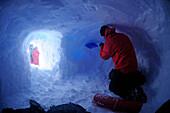 Mountaineer digging a snow cave at Collado Este, Monte Sarmiento, Cordillera Darwin, Tierra del Fuego, Chile