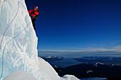 Mountaineer in the north face of Monte Sarmiento, Strait of Magellan in background, Cordillera Darwin, Tierra del Fuego, Chile
