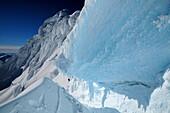 Mountaineer in the bergschrund of the north face of Monte Sarmiento, Cordillera Darwin, Tierra del Fuego, Chile