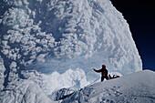Mountaineer below an ice mushroom in the north face of Monte Sarmiento, Cordillera Darwin, Tierra del Fuego, Chile