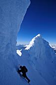 Mountaineer below an ice mushroom at the west summit of Monte Sarmiento, Cordillera Darwin, Tierra del Fuego, Chile