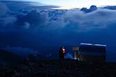 Climber with headlamp beside wilderness hut bivacco Ettore Castiglioni, Crozzon di Brenta, Brenta Dolomites, Trentino, Italia