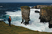 Hiker looking at Castle of Yesnaby, Mainland, Orkney Islands, Scotland, Great Britain