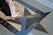 Woman placing her hands in the handprints of film star Jackie Chan on the Avenue of Stars promenade along Hong Kong Harbour waterfront, Tsim Sha Tsui, Kowloon, Hong Kong