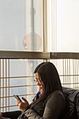 Frau mit Smartphone im Grand Cafe des Grand Hyatt Hotel im 54. Stockwerk des Jin Mao Tower Hochhaus, Pudong, Shanghai, China