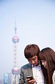 Junges Paar blickt auf Smartphone mit Oriental Pearl Tower im Hintergrund, Shanghai, China