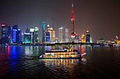 Ausflugsboot auf dem Huangpu Fluss mit Oriental Pearl Tower und Pudong Skyline bei Nacht, Shanghai, China