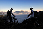 Mountain bikers on mount Feuerpalven, Untersberg in background, Berchtesgadener Land, Upper Bavaria, Germany