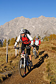 Mountain bikers cycling on mount Feuerpalven, mount Watzmann in background, Berchtesgadener Land, Upper Bavaria, Germany