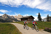 Mountain bikers passing Litzlalm, mount Hochkalter in background, Berchtesgadener Land, Upper Bavaria, Germany