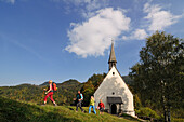 Female hikers passing Streichenkirche, Schleching, Chiemgau, Bavaria, Germany