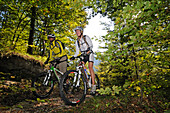 Mountain bikers passing a wooden trail, Reit im Winkl, Chiemgau, Upper Bavaria, Germany