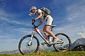 Female mountainbiker off-roading, Steinplatte, Lofer Mountains in background, Tyrol, Austria