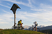 Mountain bikers resting beside a wayside cross, Winklmoosalm, Lofer Mountains in background, Chiemgau, Bavaria, Germany
