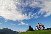 Couple with e-bikes, Wilder Kaiser mountains in background, Reit im Winkl, Chiemgau, Upper Bavaria, Germany