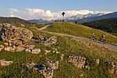 Couple riding e-bikes to Winklmoosalm, Reit im Winkl, Chiemgau, Upper Bavaria, Germany