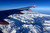 Aerial view from an aeroplane over the snowy Alps, Alps, Europe