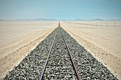 Railway tracks and endless row of electricity pylons in the desert close to Luderitz, Namibia, Africa