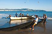 Fishermen carrying fishing nets, Playa Las Hamacas, Acapulco, Guerrero, Mexico