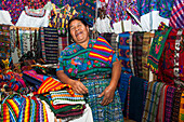 Woman offering colorful handicrafts at market stand, Antigua, Sacatepequez, Guatemala