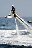 Europe, Principality of Monaco, Montecarlo Beach resort and hotel property of SBM (Societe des Bains de Mer), practising the new aquatic sport called Flyboard.