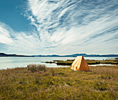 Solitary tent pitched by lakeside