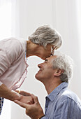 Senior woman bending to kiss man