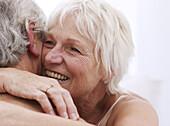 Senior couple embracing, close up