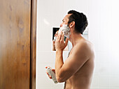 Mature man applying shaving foam in bathroom