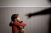 Frightened little girl and shadow of adult hand pointing at her