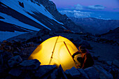 Woman unzips her tent at Camp One on Aconcagua in the Andes Mountains, Mendoza Province, Argentina