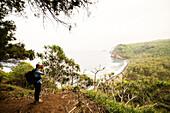 Mid adult man photographing coastline