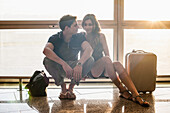 Young couple sitting on railing in airport
