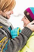 Man touching woman's face, woman wearing knit hat