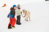 Boy and girl walking dog in snow