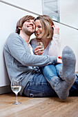 Couple sitting on kitchen floor with wine