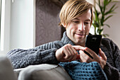 Man using smartphone on sofa in living room
