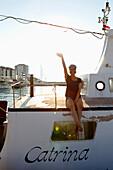 Woman sitting on yacht, waving