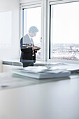 Businessman standing in office using smartphone