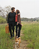 Couple with picnic basket walking dog