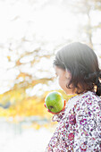 Side view of child holding green apple